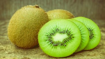 Close Up Slice Of Fresh Kiwi Fruit On Old Wood Background.