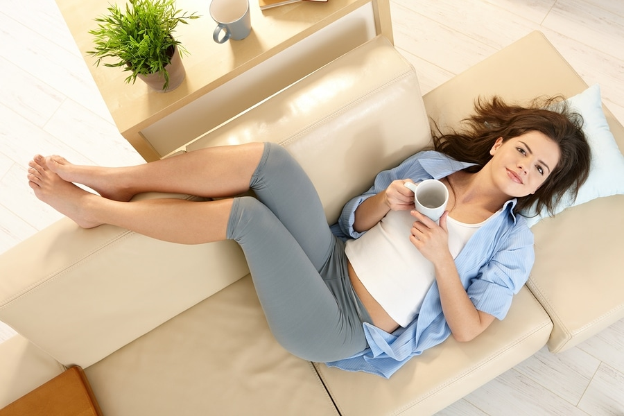 Girl resting on couch with feet up, smiling, holding coffee cup,